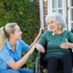 Kneeling smiling nurse attending to an elderly woman in a wheel chair
