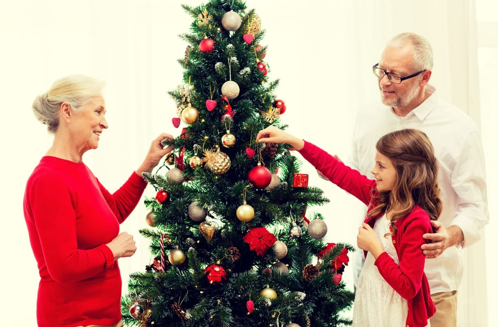 Grandparent and grandchild around Christmas tree